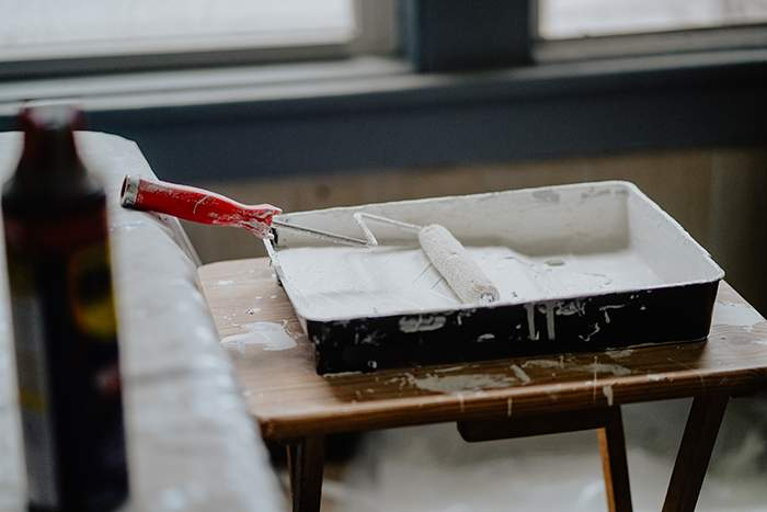 Paint roller in tray white paint renovation home improvement