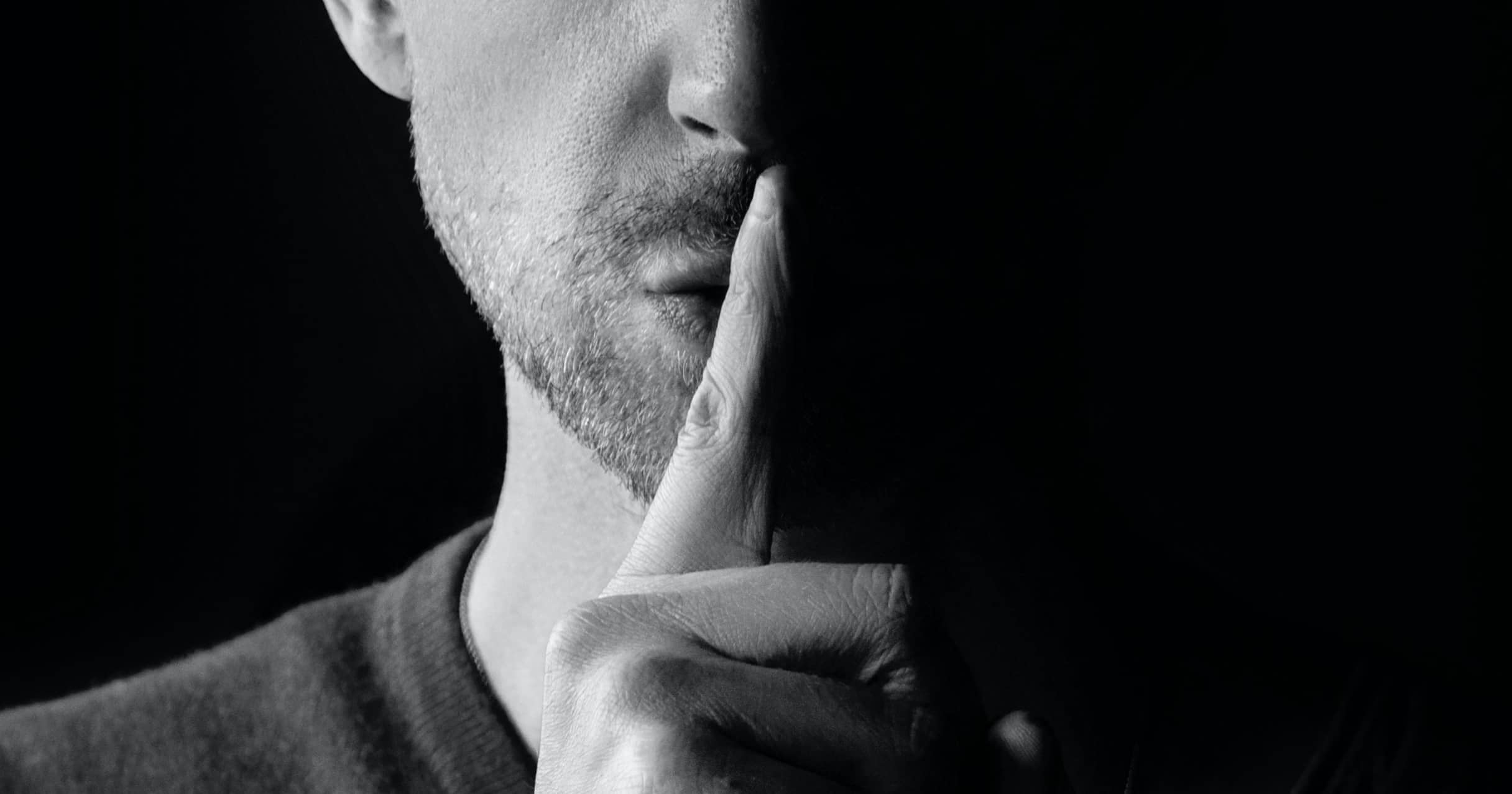 Man-finger-over-mouth-quiet-silence